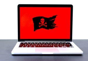 Ordenador portátil con fondo rojo y bandera pirata con calavera y huesos